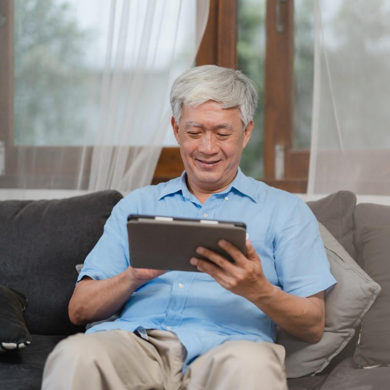Asian senior men using tablet at home. Asian Senior Chinese male search information about how to good health on internet while lying on sofa in living room at home concept.